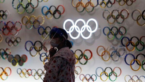 Una chica con mascarilla cerca de logo de Juegos Olímpicos (JJOO) en Tokio durante el brote de coronavirus en Japón - Sputnik Mundo