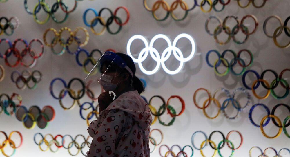 Una chica con mascarilla cerca de logo de Juegos Olímpicos (JJOO) en Tokio durante el brote de coronavirus en Japón