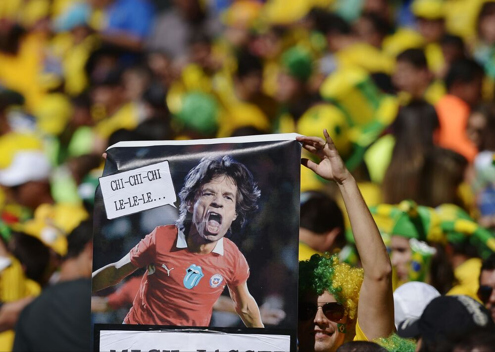 Un hincha brasileño sostiene un cartel del cantante Mick Jagger vistiendo una camiseta chilena antes del partido de fútbol de octavos de final de la Copa Mundial entre Brasil y Chile en Brasil, el 28 de junio de 2014. La estrategia del hincha fue buena, pero el resultado fue un empate 1-1. (AP Photo / Manu Fernández)