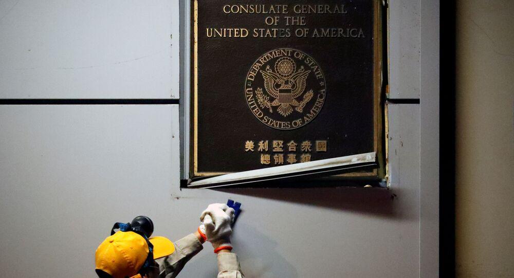 Un trabajador remueve la placa del Consulado estadounidense en la ciudad de Chengdu