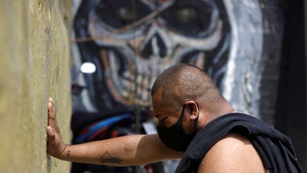 Un hombre con mascarilla rezando a la Santa Muerte en Ciudad de México - Sputnik Mundo