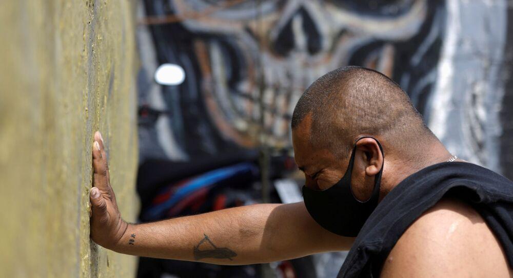 Un hombre con mascarilla rezando a la Santa Muerte en Ciudad de México