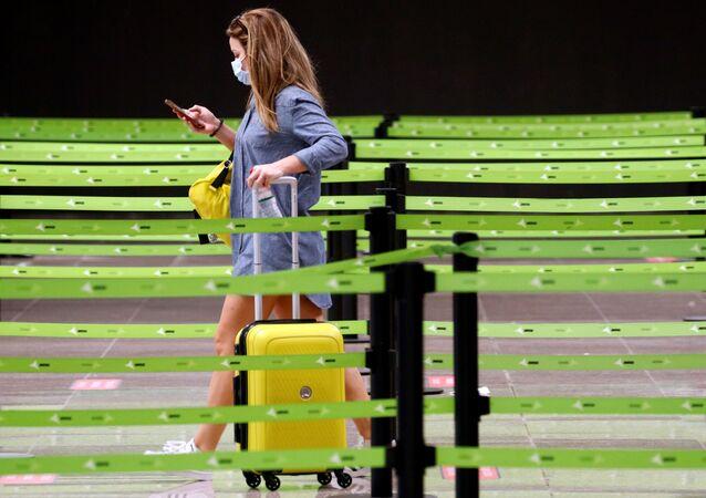 Una mujer en mascarilla en el aeropuerto El Prat de Barcelona, España