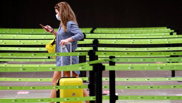 Una mujer en mascarilla en el aeropuerto El Prat de Barcelona, España - Sputnik Mundo