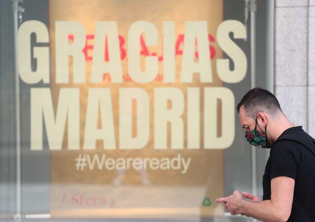 Un hombre pasa junto a una tienda que tiene un mensaje que dice Gracias Madrid. Foto de archivo.