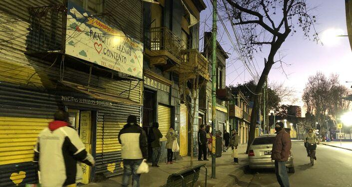 Las filas comienzan a formarse en los comedores cuando cae el atardecer en la ciudad de Buenos Aires