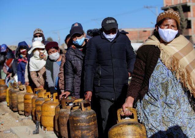 Una fila de personas con frascos de gas en La Paz