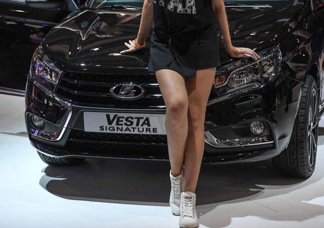 Una modelo posa delante de un Lada Vesta en el Salón del Automóvil de Moscú de 2016
