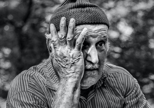 Un hombre mayor con una de las manos sobre el rostro