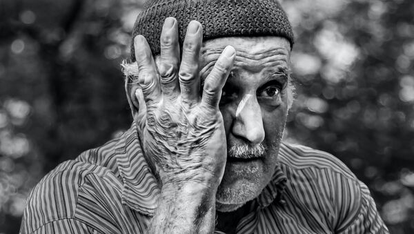 Un hombre mayor con una de las manos sobre el rostro - Sputnik Mundo