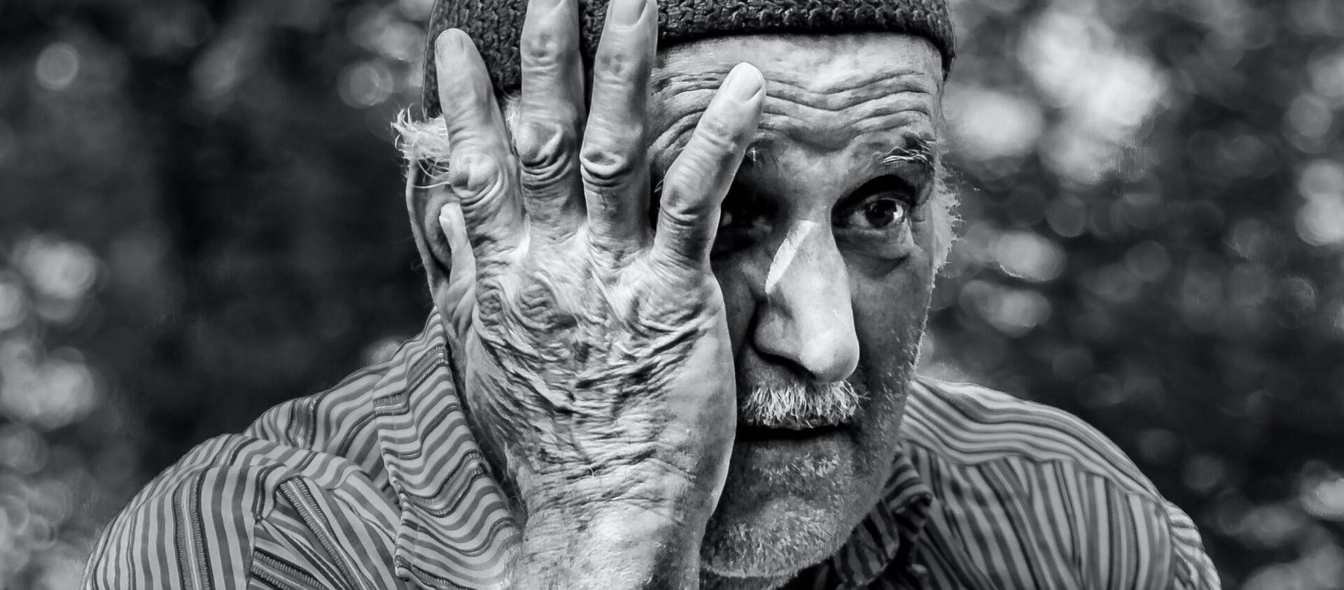 Un hombre mayor con una de las manos sobre el rostro - Sputnik Mundo, 1920, 03.08.2020