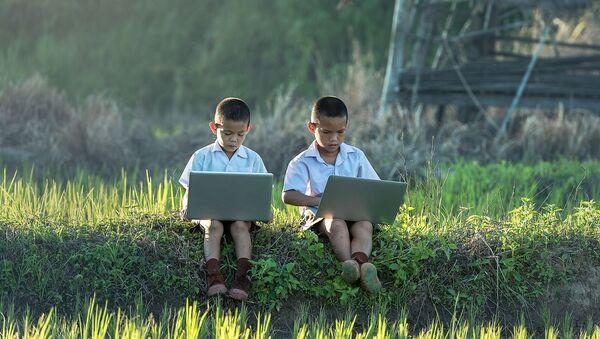 Dos niños usando ordenadores portátiles - Sputnik Mundo