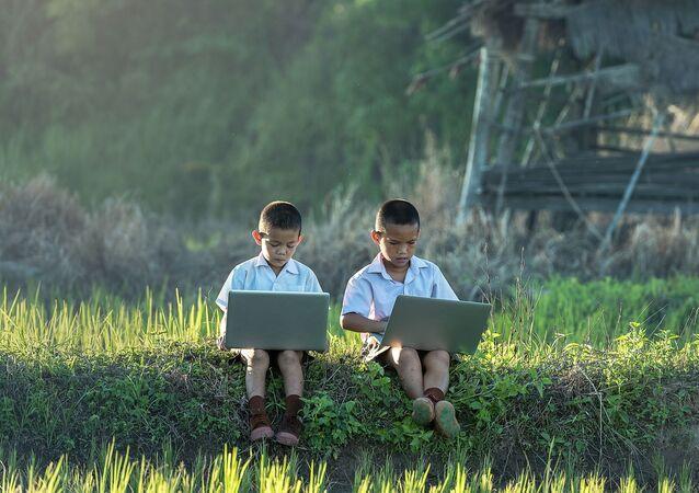 Dos niños usando ordenadores portátiles