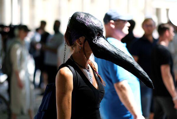 Девушка в маске чумного доктора на демонстрации против связанных с коронавирусом ограничений в Берлине  - Sputnik Mundo
