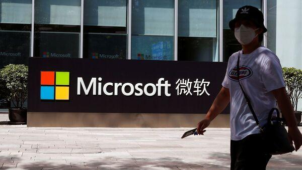 Una persona pasa junto a un logo de Microsoft en la oficina de Microsoft en Pekín - Sputnik Mundo