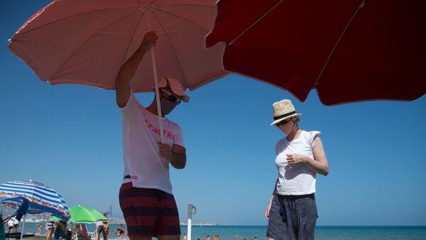 Una pareja coloca una sombrilla en una playa de Málaga - Sputnik Mundo