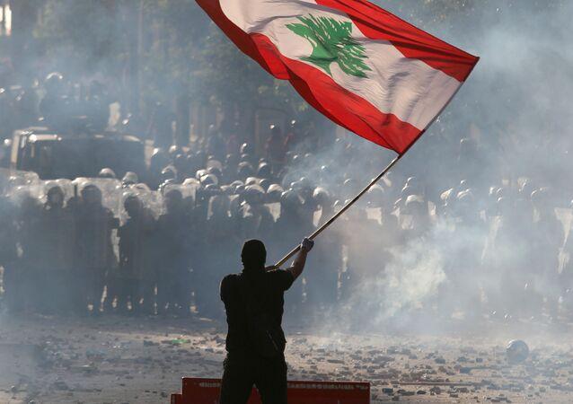 Un manifestante sostiene la bandera del Líbano durante las multitudinarias protestas contra la gestión del Gobierno tras la explosión en el puerto de Beirut, el 8 de agosto de 2020