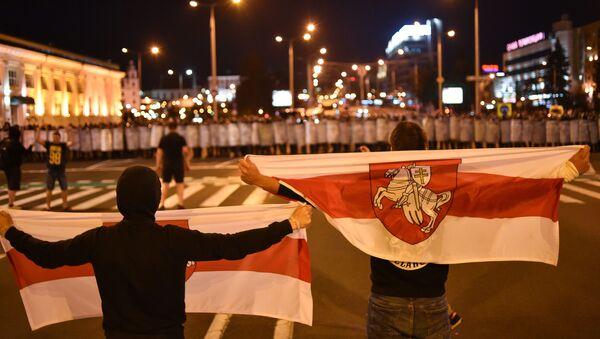 Manifestantes se paran en frente de la Policía durante una protesta en Minsk - Sputnik Mundo