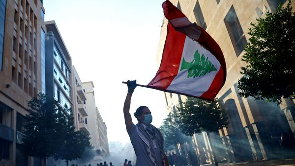 Un hombre con la bandera del Líbano durante las protestas en Beirut - Sputnik Mundo