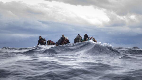 Inmigrantes en medio del mar Mediterráneo a punto de ser rescatados por la ONG española Open Arms. Enero 2020 - Sputnik Mundo