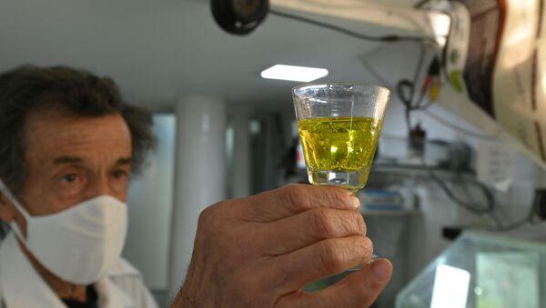 Farmacéutico boliviano con un vaso de dióxido de cloro - Sputnik Mundo