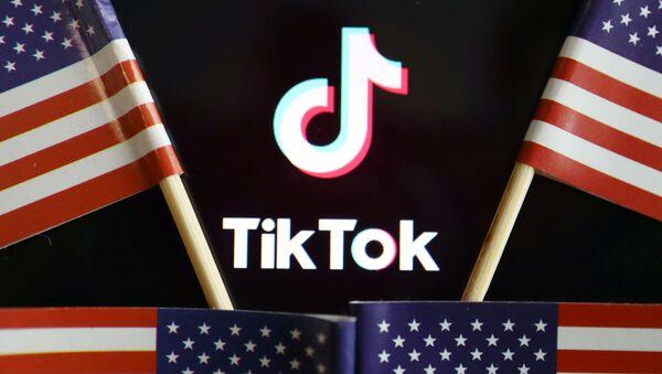 El logo de TikTok junto a banderas estadounidenses - Sputnik Mundo