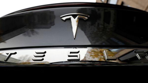 El logo de Tesla en un automóvil de la marca - Sputnik Mundo