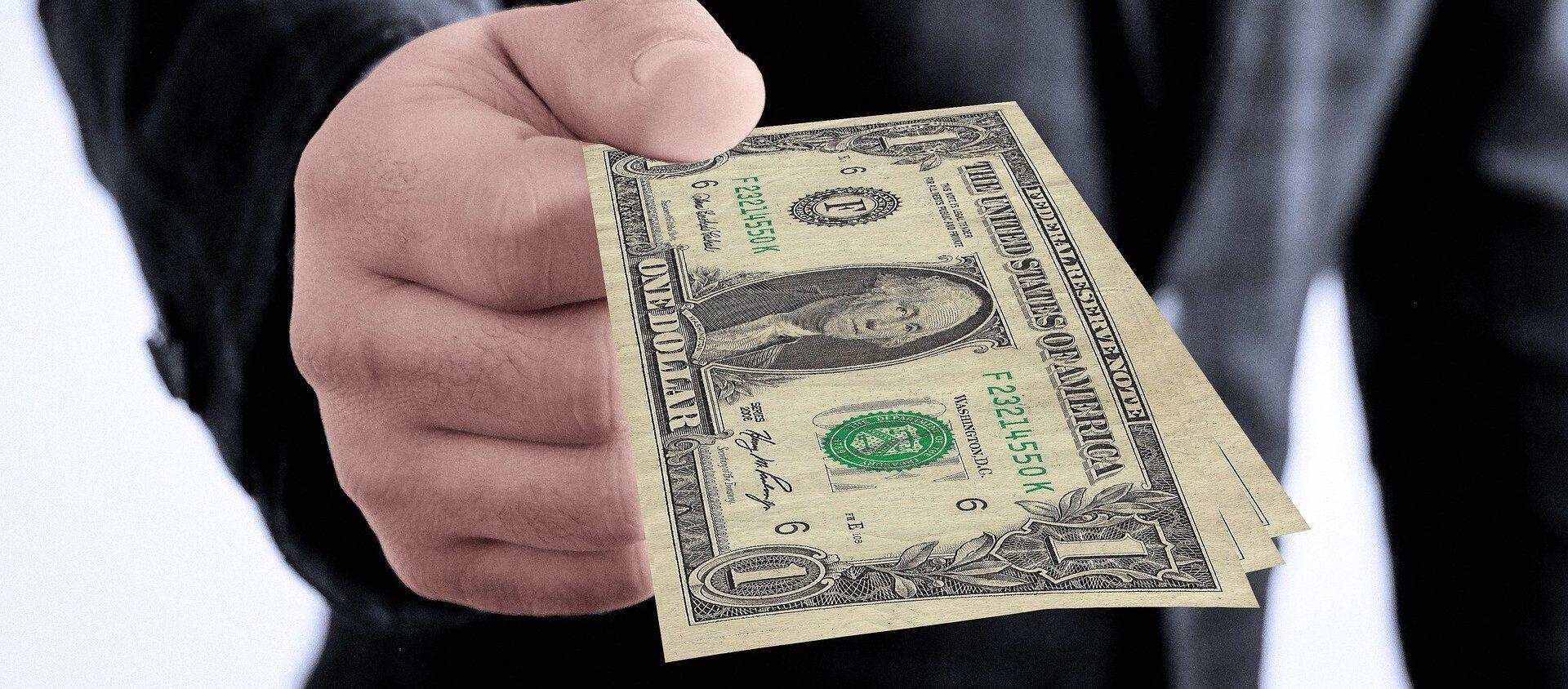 Una persona dando dinero - Sputnik Mundo, 1920, 08.12.2020