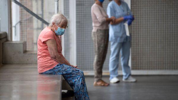 Una anciana espera ser examinada en un centro médico - Sputnik Mundo