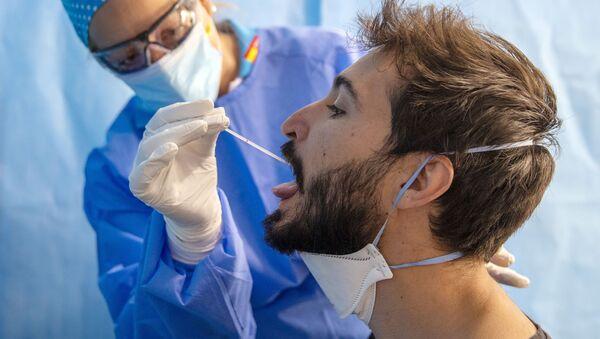 Un trabajador de la salud toma una muestra para una prueba de PCR para el  en un centro médico - Sputnik Mundo