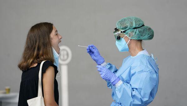 Una mujer realizándose una prueba PCR - Sputnik Mundo