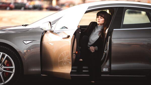 Una mujer en el interior de un vehículo de la marca Tesla - Sputnik Mundo