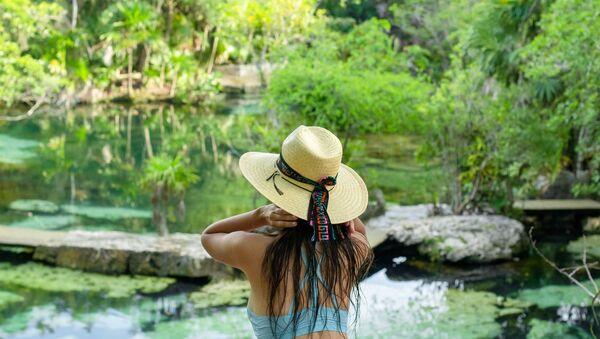 Una mujer disfruta de la vista en un cenote, México  - Sputnik Mundo