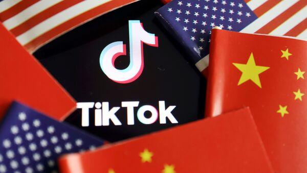 Logo de la aplicación china TikTok y banderas de EEUU y de China - Sputnik Mundo