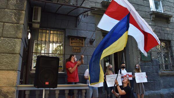 Una bandera de Ucrania y una bandera de la oposición bielorrusa en una manifestación en Kiev - Sputnik Mundo