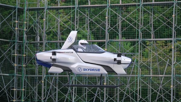 El auto volador de SkyDrive con una persona a bordo durante una prueba de vuelo  - Sputnik Mundo