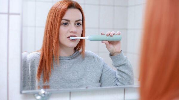 Una chica cepillándose los dientes - Sputnik Mundo