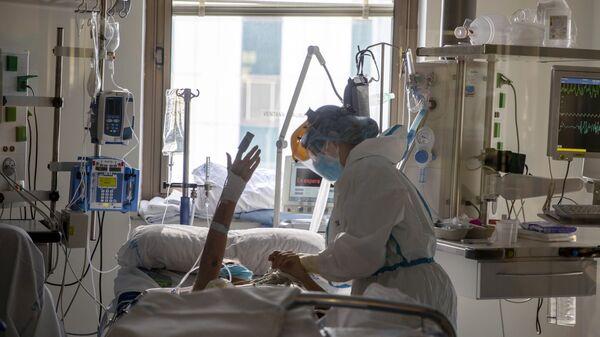 Trabajadores sanitarios asisten a un paciente con COVID-19  - Sputnik Mundo