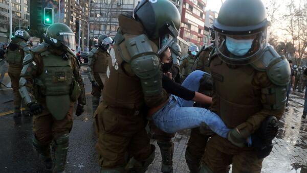 Carabineros deteniendo a una manifestante en Santiago, Chile - Sputnik Mundo