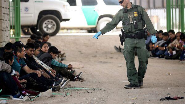 Un agente de Aduanas y Protección Fronteriza de Estados Unidos junto a migrantes detenidos en El Paso, EEUU - Sputnik Mundo