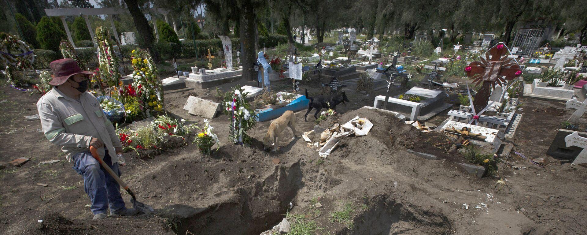 Un trabajador cava tumbas en la sección del COVID-19 del cementerio en las afueras de la Ciudad de México - Sputnik Mundo, 1920, 22.05.2021