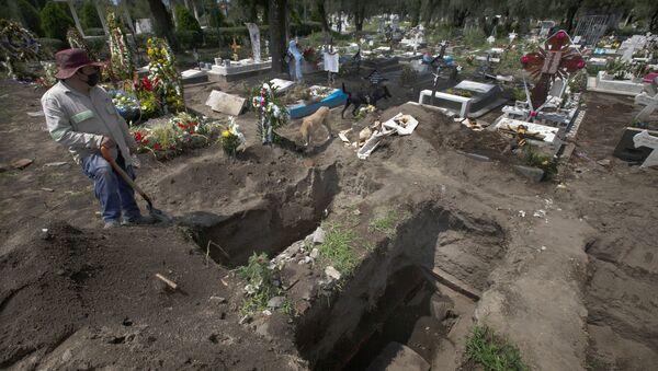 Un trabajador cava tumbas en la sección del COVID-19 del cementerio en las afueras de la Ciudad de México - Sputnik Mundo
