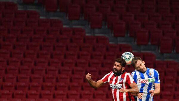 Diego Costa (Atlético de Madrid) y Diego Llorente (Real Sociedad) luchan por un balón frente a un vacío Wanda Metropolitano - Sputnik Mundo