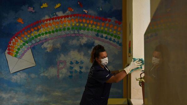 Una trabajadora de la limpieza prepara un aula en un colegio de Madrid - Sputnik Mundo
