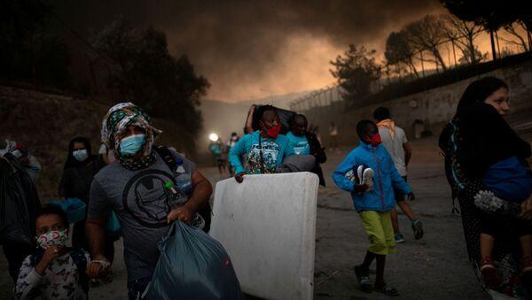 Refugiados se escapan del campo de refugiados de Moria en llamas - Sputnik Mundo
