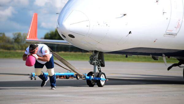 el atleta ruso Serguéi Agadzhanián establece un récord de fuerza al arrastrar un enorme avión en el aeropuerto de Kazán - Sputnik Mundo