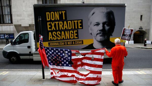 Un manifestante sostiene una bandera rota de EEUU al lado de un cartel en contra de la extradición del fundador de WikiLeaks, Julian Assange  - Sputnik Mundo