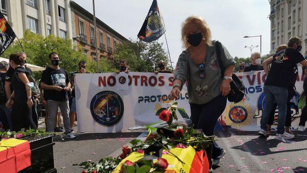 Manifestante depositando una flor sobre un ataúd durante la concentración de la policía española - Sputnik Mundo