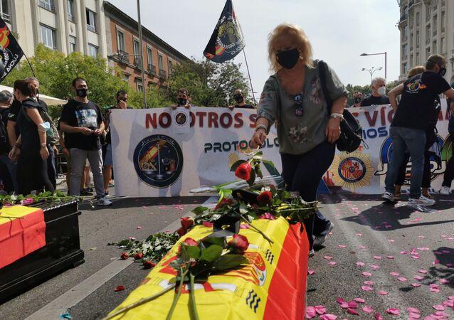 Manifestante depositando una flor sobre un ataúd durante la concentración de la policía española