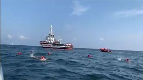 Migrantes saltan al agua del barco Open Arms - Sputnik Mundo